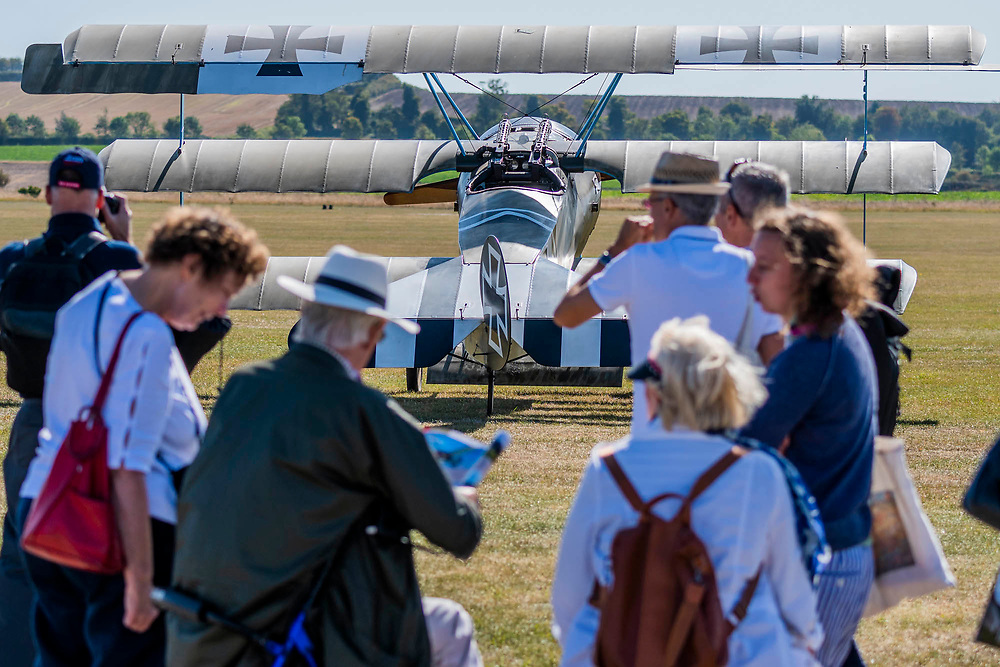 Visitors enjoying a german WW! tri-plane from the Bremont war display team - Duxford Battle of Britain Air Show at the Imperial War Museum. Also commemorating the 50th anniversary of the 1969 Battle of Britain film. It runs on Saturday 21 & Sunday 22 September 2019