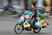 Cholon (Chinatown). Motorcycles during morning rushhour. Man transporting vegetables to the market on his bike.