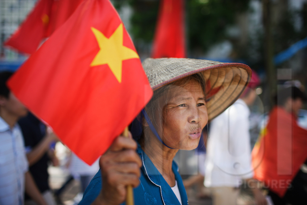 An elderly woman waves a Vietnamese flag in protest of China's invasion into Vietnam, Hanoi, Vietnam, Southeast Asia