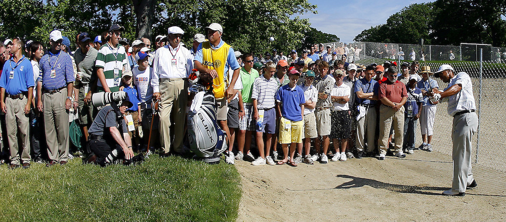 Tiger Woods of the US hits from the edge of the gallery after taking a drop on the sixteenth hole during the second day of the US Open Golf Championship at Winged Foot Golf Club in Mamaroneck, New York Friday, 16 June 2006.