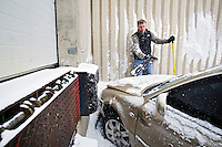 Judd Jones, the production manager for the Coeur d'Alene Press, removes debris from in front of a wrecked car Wednesday at the Coeur d'Alene Press loading dock where it crashed into the building. The driver, who was driving without a license, lost control of the vehicle in the snow on Second Street after turning off of Coeur d'Alene Avenue. There were no injuries reported in the accident.