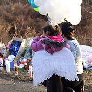 A young girl wearing angel wings arrive to pay their respects to the shrine created under the school sign in Sandy Hook after yesterday's shootings at Sandy Hook Elementary School, Newtown, Connecticut, USA. 15th December 2012. Photo Tim Clayton