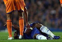 Photo: Paul Thomas.<br /> Chelsea v Barcelona. UEFA Champions League, Group A. 18/10/2006.<br /> <br /> Didier Drogba (Blue) of Chelsea lays injured on the ground by Edmilson (L).