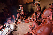 Traditionally dressed Himba women sit around a fire at their home in Okapembambu village, northwestern Namibia.  Like most traditional Himba women, they cover themselves from head to toe with an ochre powder, cow butter blend.