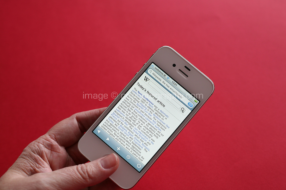 Person using a white iPhone 4s to read wikipedia