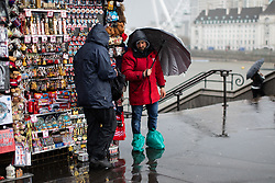 © Licensed to London News Pictures. 04/04/2019. London, UK. A shop vendor stands with plastic bags over his feet as heavy rain falls in Westminster. Photo credit : Tom Nicholson/LNP