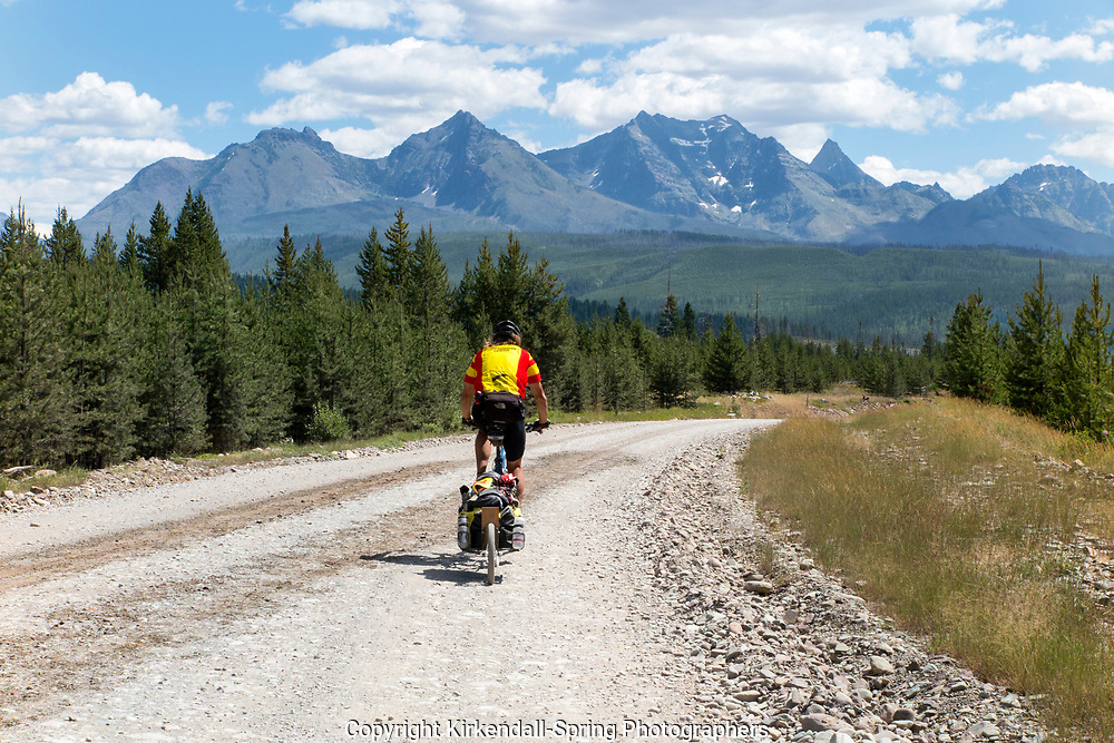 BC00641-00...MONTANA -  Tom Kirkendall cycling the Great Divide Mountain Bike Route on forest road 486 aproching Polebridge with the mountains of Glacier National Park in the distance. (MR# K1)