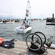Skipper Sarah Everhart Skeels, Tiverton, RI, and Cindy Walker, Middletown, RI, the only all female team competing in The Skud 18 class, leave the dock for competition with Sarah Everhart Skeels wheelchair on the dock during the C. Thomas Clagett, Jr. Memorial Clinic & Regatta at Newport, Rhode Island hosted by Sail Newport at Fort Adams. <br /> The Clagett is North America's premier event for sailors with disabilities with sailors competing in the 3 Paralympic class boats and is an integral part of preparation for athletes preparing for  Paralympic and world championship racing. Newport, Rhode Island, USA. 26th June 2015. Photo Tim Clayton