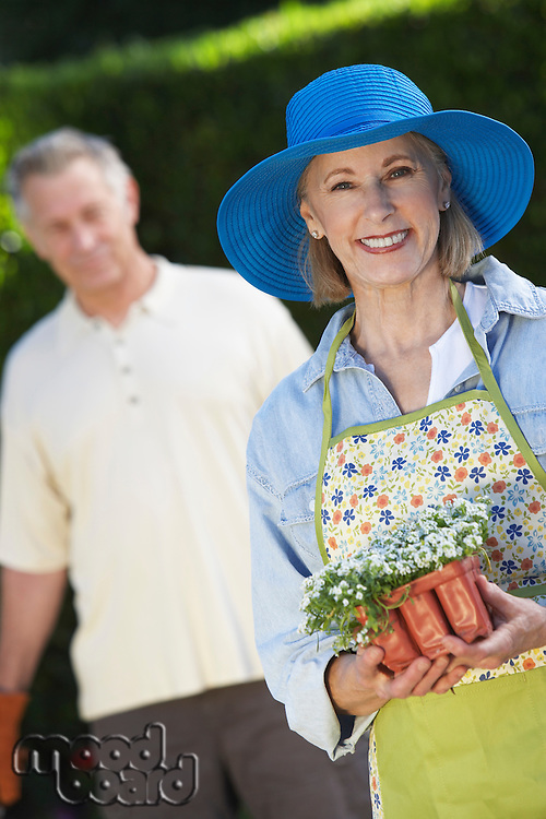 Portrait of senior woman with flowers, out of focus man in background