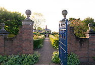 A view through a gate down a long path through broders to the house the Laskett Gardens, Much Birch, Herefordshire, UK