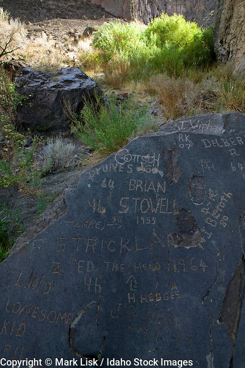 Names etched into a smooth piece of basalt lays in the bottom of Cougar Creek in Arch Canyon, Owyhee Canyonlands, Idaho.