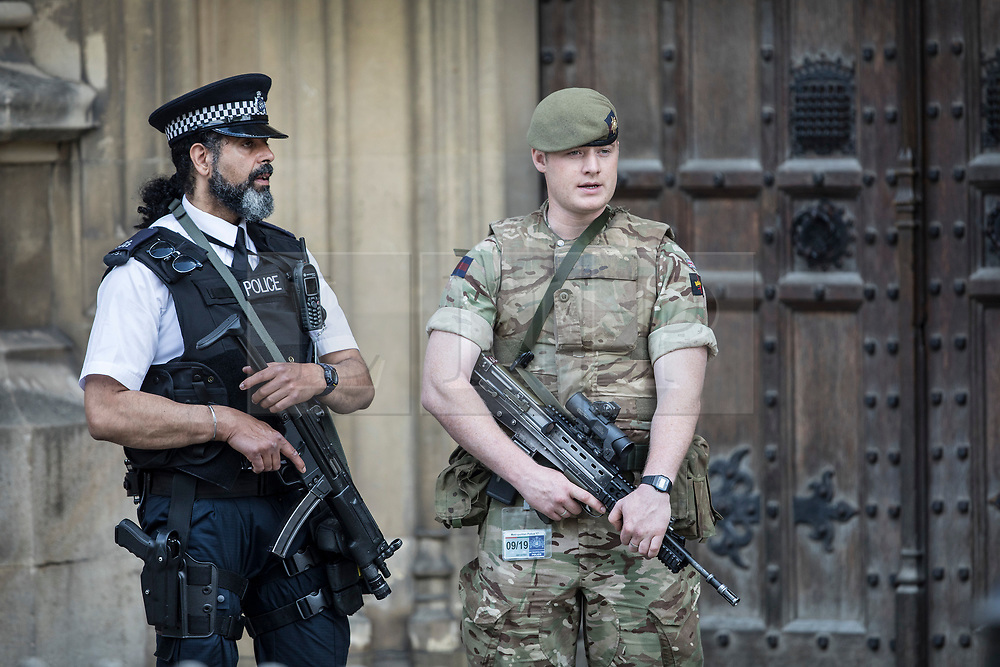© Licensed to London News Pictures. 25/05/2017. London, UK. An armed soldier stands on guard duty with a policeman at Parliament following a terrorist attack in Manchester, northern England, earlier this week.   23 people were killed an dozens more injured when Salman Abedi denonated a suicide bomb at an Ariana Grande concert. Photo credit: Peter Macdiarmid/LNP