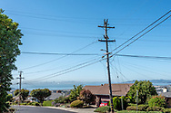 PG&E power lines and cables intersect at a power pole in an El Cerrito, California, neighborhood. San Francsico Bay and downtown are in the distance.