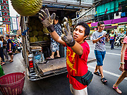 "18 MAY 2017 - BANGKOK, THAILAND: A worker delivers durian to a street food stall on Yaowarat Road in Bangkok. City officials in Bangkok have taken steps to rein in street food vendors. The steps were originally reported as a ""ban"" on street food, but after an uproar in local and international news outlets, city officials said street food vendors wouldn't be banned but would be regulated, undergo health inspections and be restricted to certain hours on major streets. On Yaowarat Road, in the heart of Bangkok's touristy Chinatown, the city has closed some traffic lanes to facilitate the vendors. But in other parts of the city, the vendors have been moved off of major streets and sidewalks.      PHOTO BY JACK KURTZ"