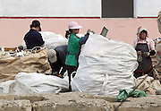 """North Korean women sift through Chinese garbage, in order to recycle some of the materials in the town of Sinuiju July 8, 2006. China and North Korea are separated by the Yalu River, upon which Chinese tourists take pleaure cruises across the water to  observe their less economically developed neighbors.  North Korea has threatened to take """"stronger physical actions"""" after Japan imposed punitive measures in response to its barrage of missile tests and pushed for international sanctions. North Korea has vowed to carry out more launches and has said it will use force if the international community tries to stop it. DPRK, north korea, china, dandong, border, liaoning, democratic, people's, rebiblic, of, korea, nuclear, test, rice, japan, arms, race, weapons, stalinist, communist, kin jong il"""