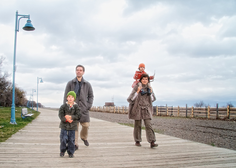 A young family walks on the boardwalk in spring, Toronto, Canada