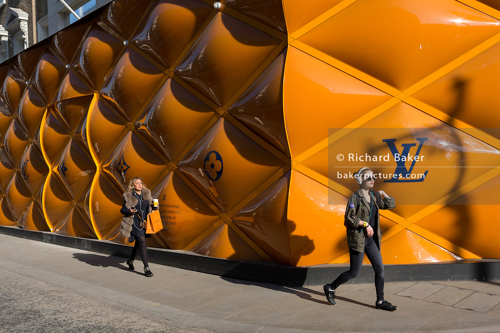Women shoppers walk past the temporary renovation hoarding of luxury brand Louis Vuitton in New Bond Street, on 27th February 2019, in London, England.