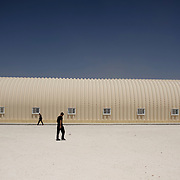 August 09, 2013 - Zarqa, Jordan: Two syrian refugees walk by an hangar used as communal kitchen at Mrigb Al-Fuhud refugee camp, also known as Emirates-Jordanian camp, 20 kilometres east of the Jordanian city of Zarqa.<br /> The 10 million USD camp, which has 750 caravans, a hospital, and a school and can take up to four thousand people, first opened in April 2013 and was paid for by the United Arab Emirates. Work is underway to house a total of 20 thousand by the end of the year. <br /> In contrast with the two other camps in the area, Mrigb Al-Fuhud as been classified by many as a 'five star' camp due to impressive housing facilities provided to the refugees. (Paulo Nunes dos Santos/Al Jazeera)