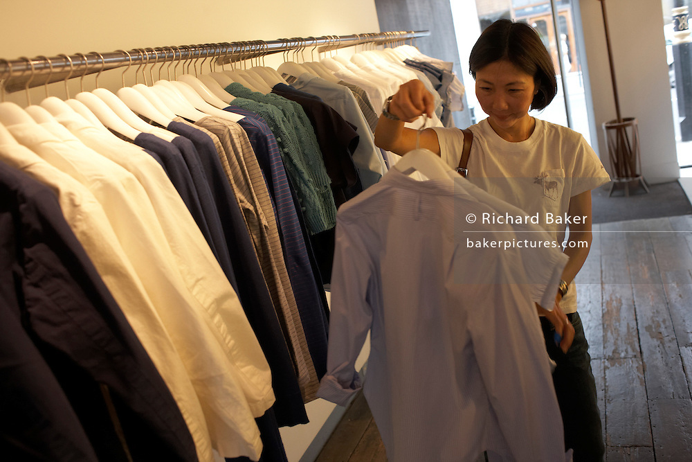 A customer tries on summer shirts at British couturier Margaret Howell's flagship Wigmore Street London shop