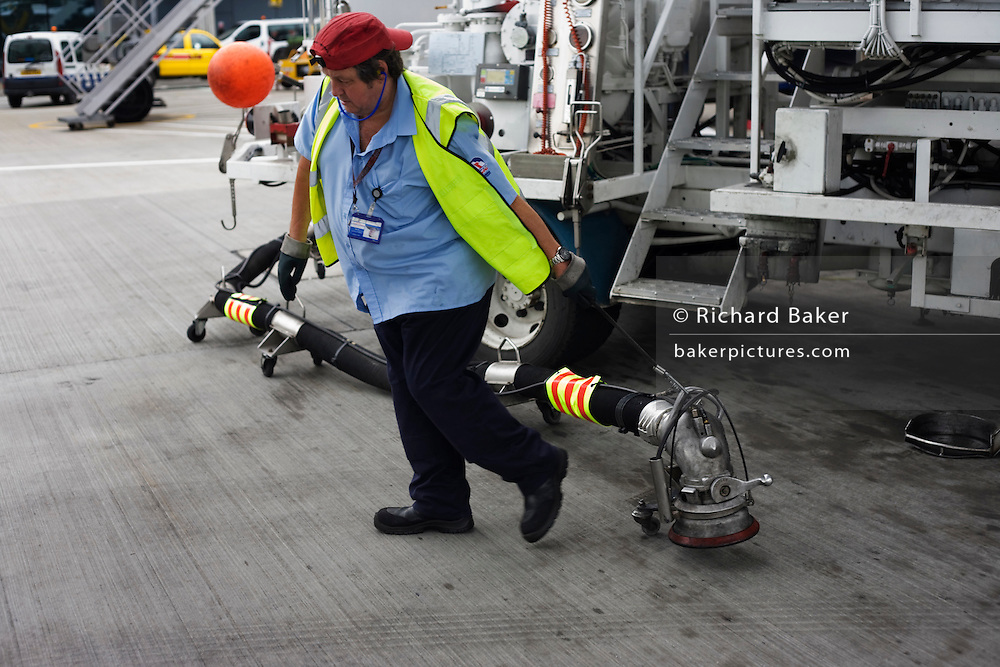 """During the turnround of the British Airways jet aircraft, a refueller drags the heavy fuel nozzle from his bowser truck on the apron at Heathrow Airport's Terminal 5. He is about to plug the connections into the airfield's underground reservoirs from where some 109 tons of Jet A1 aviation fuel flowing at a rate of 3,000 litres a minute will be uplifted into the wing tanks of a Boeing 747-300, a typical quantity of extra fuel for this aeroplane bound for Los Angeles. From writer Alain de Botton's book project """"A Week at the Airport: A Heathrow Diary"""" (2009). ."""