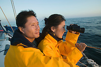 Couple wearing yellow anoraks on yacht woman looking through binoculars