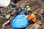 A family identifies the body of a relative found in the town of Rikuzen Takada during a search for bodies after the earthquake and tsunami hit the city on 11 March 2011.
