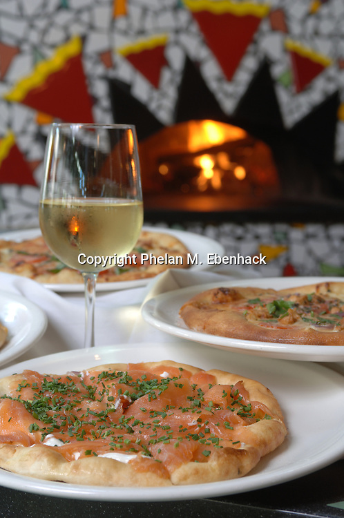 A Smoked Salmon Pizza with dill cream, red onion, chili oil and chives, among a variety of gourmet pizzas.