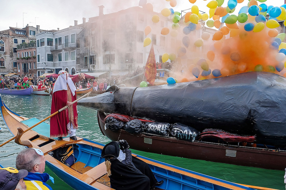 "VENICE, ITALY - FEBRUARY 16:  The ""Pantegana""  (Big Rat)  release ballons and smoke on Canaregio Canal at the end of the traditional regatta which officially opens the Carnival  on February 16, 2014 in Venice, Italy. The 2014 Carnival of Venice will run from February 15 to March 4 and includes a program of gala dinners, parades, dances, masked balls and music events.  (Photo by Marco Secchi/Getty Images)"