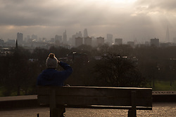 Primrose Hill, London, February 15th 2015. A woman takes in the view of London's skyline as the sun breaks through the clouds on a chilly early morning on Primrose Hill, overlooking London&rsquo;s skyline.<br /> ///FOR LICENCING CONTACT: paul@pauldaveycreative.co.uk TEL:+44 (0) 7966 016 296 or +44 (0) 20 8969 6875. &copy;2015 Paul R Davey. All rights reserved.
