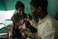 "RENDEL, HAITI - OCTOBER 12, 2016:  Jean Romit Cadet, 22, feeds his pregnant wife Leonette Reive, 18, who is sick with Cholera, blowing on each spoonful of porridge before putting it in her mouth.  ""I spent the night here with her but the bed is too small for both of us so I slept outside and checked on her every hour,"" he said.  ""If I get sick, I get sick.  I'm responsible for her."" The small clinic in Rendel, Haiti is overflowing with Cholera patients, and more keep coming. For days, aid groups and officials have warned of a coming Cholera outbreak that could affect as many as 500,000 Haitians.  The town of Rendel and its surroundings, which once sheltered 25,000 people, is an epicenter of the coming disaster."