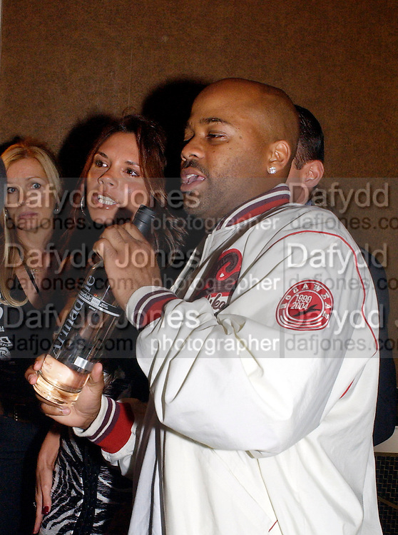 Damon Dash with a bottle of the vodka he is promoting and  Victoria Beckham, Rocawear UK launch, 5 Cavendish Sq. © Copyright Photograph by Dafydd Jones 66 Stockwell Park Rd. London SW9 0DA Tel 020 7733 0108 www.dafjones.com