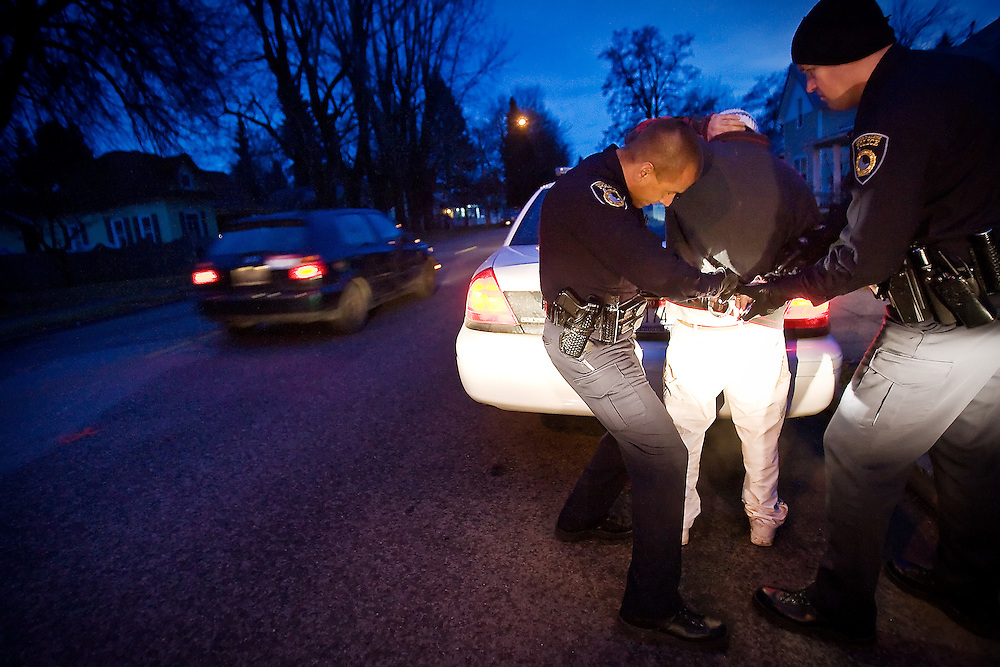 JEROME A. POLLOS/Press..Coeur d'Alene Police officers Jason Matheney, left, and Hank Dunham arrest a suspect for felony eluding Friday.