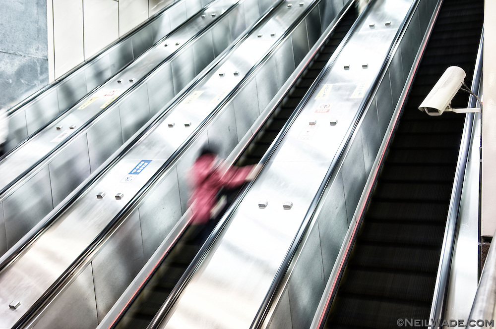 A lone woman rides up a long escalator in Taipei, Taiwan.