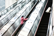 A lone woman rides up a long escalator in Taipei, Taiwan.