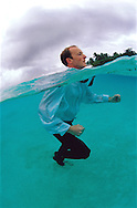 Up to your Neck in water, a man fully dressed in business clothes , with just his head above water.