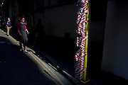 A woman approaches a sunlit post and warning tape in a City of London street.