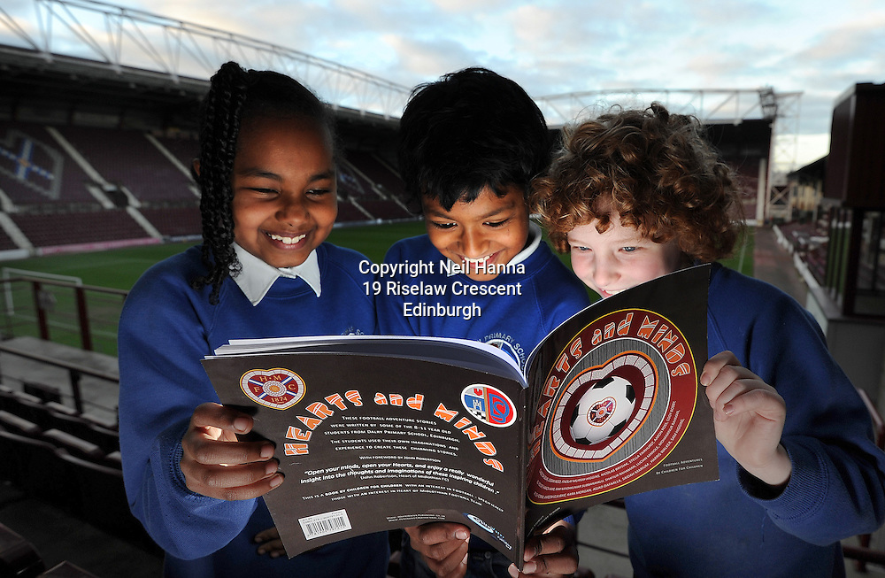 JP License<br /> Wednesday 3 December, Tynecastle Park<br /> <br /> Pic Caption<br /> Asjad Dafaalla, Mohaiminur Rahman and Harris Walker enjoy reading their book!<br /> <br /> Heart of Midlothian FC help local Edinburgh primary school pupils launch a <br /> special book of footballing stories written by the children.<br /> &lsquo;Hearts and Minds&rsquo; is a collection of tales penned by the P5-7 pupils at Dalry Primary <br /> School, which is just around the corner from the Tynecastle club.<br /> They put the short stories together with the help of local author Mary Turner <br /> Thomson and P7 teacher Graeme Hawkins.<br /> <br />  Neil Hanna Photography<br /> www.neilhannaphotography.co.uk<br /> 07702 246823
