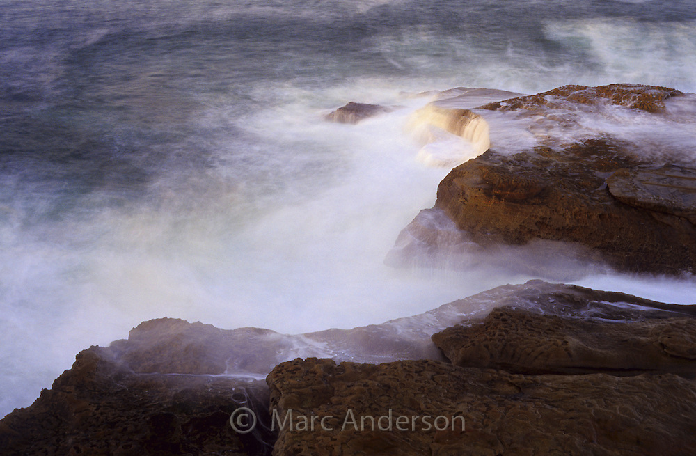 Waves broken against a rocky coastline, Australia.
