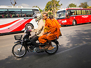 25 FEBRUARY 2015 - PHNOM PENH, CAMBODIA: Buddhist monks ride a motorcycle in Phnom Penh.     PHOTO BY JACK KURTZ