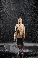 Woman standing in rain not Using Her Umbrella
