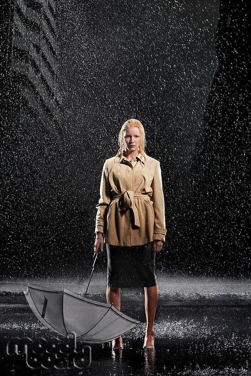 Woman standing in rain not Using Her Umbrella