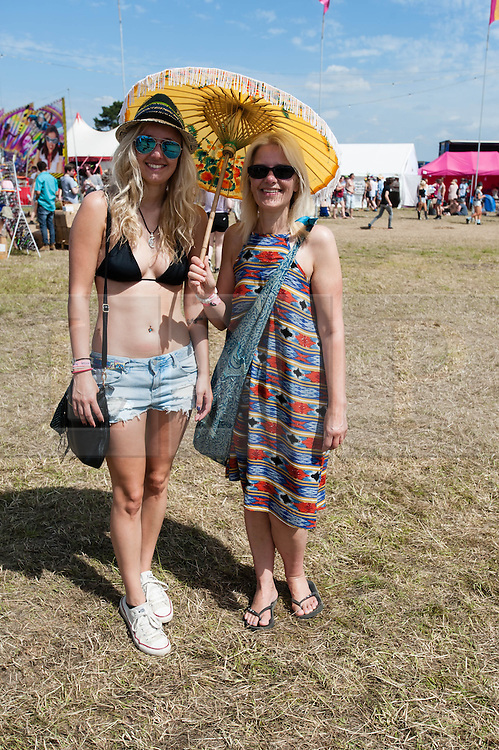 © Licensed to London News Pictures. 13/06/2014. Isle of Wight, UK.  Festival goers  use an umbrella to shelter from  the hot morning sun at the Isle of Wight Festival 2014.   Today is expected to be the hottest day of the year.  The Isle of Wight festival is an annual music festival that takes place on the Isle of Wight. Photo credit : Richard Isaac/LNP
