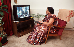 Woman with hearing impairment watching television with subtitles,