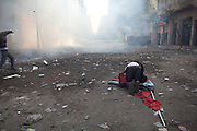 A man prays on an Egyptian flag as Egyptian police clashed with anti-government protesters for a fifth day in central Cairo Wednesday as a rights group raised the overall death toll from the ongoing unrest to 38..The clashes came one day after tens of thousands of protesters in Tahrir Square rejected a promise by Egypt's military ruler to speed up a presidential election to the first half of next year. (Photo by Heidi Levine/Sipa Press).