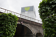 The covered remains of the Grenfell high-rise Grenfell, on the first anniversary of the tower block disaster, on 14th June 2018, in London, England. 72 people died when the tower block in the borough of Kensington & Chelsea were killed in what has been called the largest fire since WW2. The 24-storey Grenfell Tower block of public housing flats in North Kensington, West London, United Kingdom. It caused 72 deaths, out of the 293 people in the building, including 2 who escaped and died in hospital. Over 70 were injured and left traumatised. A 72-second national silence was held at midday, also observed across the country, including at government buildings, Parliament.