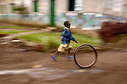 A boy plays with a discarded tire during a rain shower in the genocide survivors village of Rugerero Rwanda.