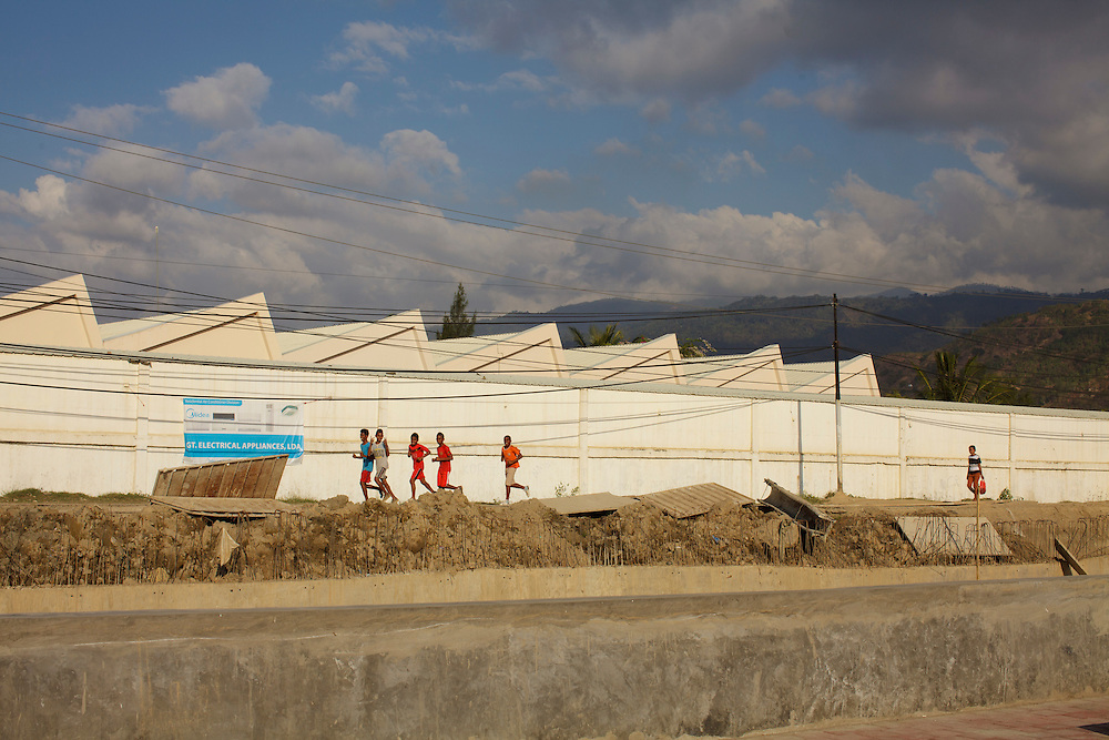 Boys jogging behind a warehouse in Dili, East Timor.