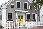 Traditional clapboard cottage with bright yellow front door and white paling fence at Provincetown, Cape Cod, New England, USA