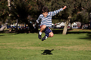 Authentic action of a young happy boy jumps in the park - copy space to sides