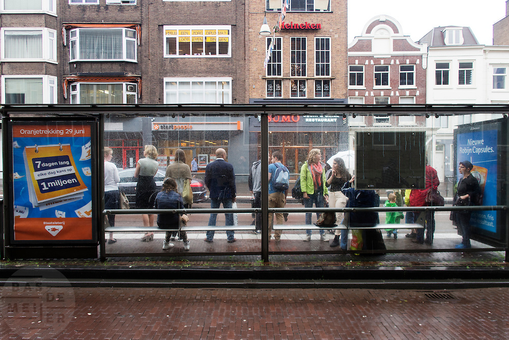 In Utrecht schuilen reizigers bij de bushalte tegen de stromende regen.<br /> <br /> In Utrecht travelers are seeking shelter at a bus stop for the pouring rain.